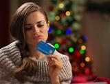 Thoughtful woman in front of Christmas tree holding credit card