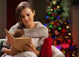 Woman in chair in front of Christmas tree reading book