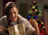 Smiling woman in front of Christmas tree looking in shopping bag