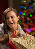 Smiling woman with shopping bag in front of Christmas lights