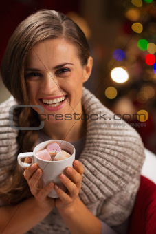 Smiling woman holding cup of hot chocolate with marshmallows