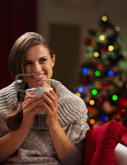 Happy young woman with cup of hot chocolate in front of Christmas lights