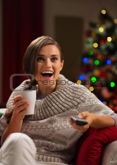 Surprised young woman with cup of hot beverage looking TV