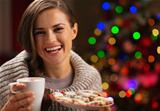 Happy woman holding cup of hot chocolate with marshmallows and plate of Christmas cookies
