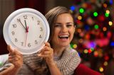 Happy woman showing clock in front of Christmas tree