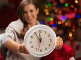 Closeup on clock in hand of happy woman in front of Christmas tree