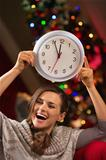 Cheerful woman showing clock in front of Christmas tree