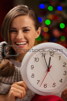 Portrait of smiling woman showing clock in front of Christmas lights