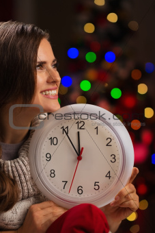 Portrait of happy woman showing clock in front of Christmas lights