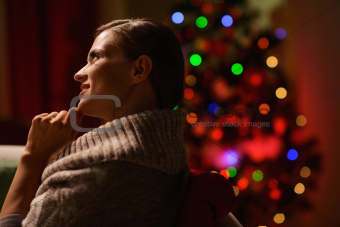 Thoughtful woman sitting chair in front of Christmas tree