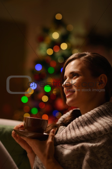 Thoughtful woman sitting chair and drinking hot beverage in front of Christmas tree