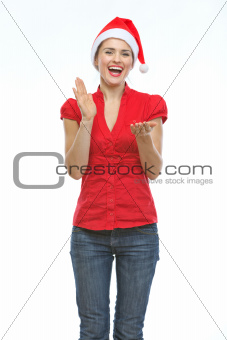 Happy young woman in Christmas hat clapping hands