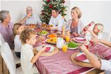 Family having christmas dinner together at table in kitchen