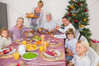 Mother bringing turkey to dinner table at christmas