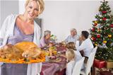 Proud mother showing roast turkey at christmas