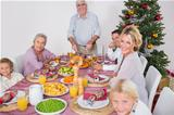 Happy family at christmas dinner with grandfather carving the turkey