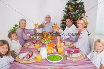 Family raising their glasses at christmas at dinner