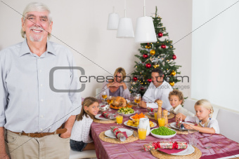 Smiling grandfather standing at the dinner table at christmas