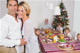 Husband and wife embracing beside the dinner table at christmas