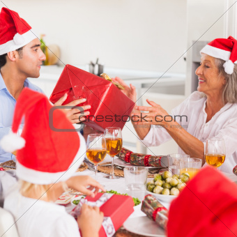 Family exchanging christmas presents around the dinner table wearing santa hats
