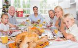 Focus on the roast turkey in front of family at chrismas dinner