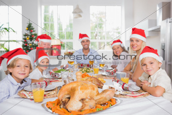 Happy family wearing santa hats around the dinner table at christmas
