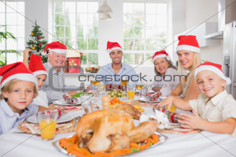 Smiling family around the dinner table at christmas wearing santa hats