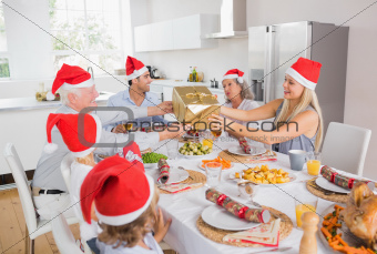 Festive family exchanging gifts at christmas at the dinner table