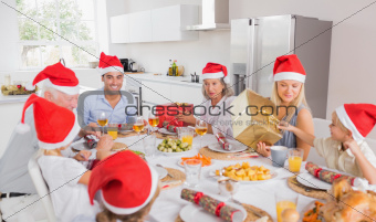 Smiling family at the dinner table at christmas exchanging gifts wearing santa hats