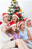 Extended family singing christmas carols together on couch