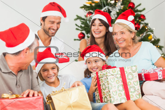 Happy family at christmas swapping gifts on the couch