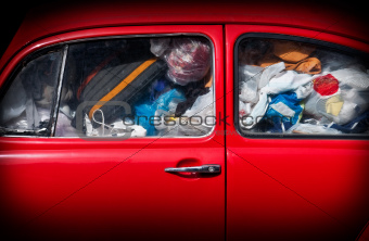 A red car with rubbish.