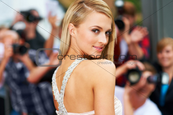 Rear-view portrait of a stunning actress walking the red carpet at her movie premiere