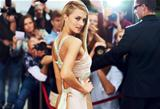 A stunning actress walking the red carpet at her movie premiere surrounded by fans and the press