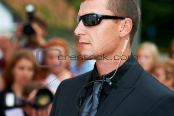 A security guard wearing dark glasses and an earpiece standing in front of the paparazzi