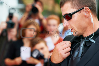 A security guard wearing dark glasses talking into his radio on the red carpet at a movie premiere - Copyspace