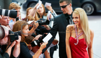 A stunning starlet in a red dress walking down the red carpet inundated by the requests of her fans and the press