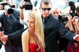 A beautiful actress posing on the red carpet amidst paparazzi and their flashing cameras