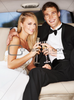 """A young, blissfully happy couple enjoying champagne together in the back of a limousine"""