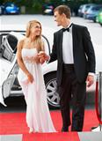A sylish young couple emerging from a luxurious white stretch limousine onto the red carpet