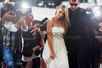 A glamorous starlet in an angelic white dress being ushered down a chaotic red carpet