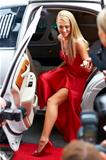 A gorgeous young starlet emerging from a white limousine onto the red carpet