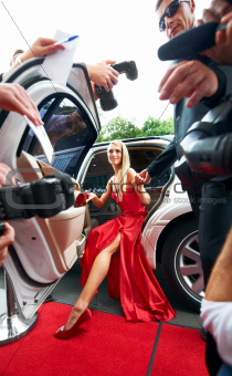 Paparazzi-view of a gorgeous young starlet emerging from a white limousine onto the red carpet