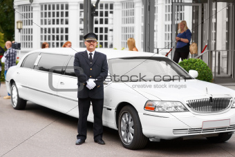 A proud chaffeur standing beside a white stretch limousine