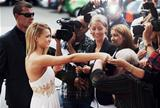 A stunning young actress signing autographs on the red carpet while swamped by paparazzi