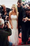 A glamorous starlet in an angelic white dress making her way down a chaotic red carpet