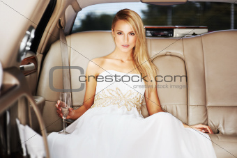 Portrait of a high society young beauty holding champagne in the back of a limousine