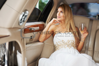 A gorgeous young woman enjoying a glass of champagne while sitting in the luxury of a limousine