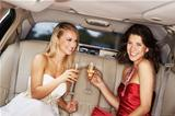 Two gorgeous young woman enjoying champagne in the back of a stretch limousine