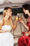 Two young woman clinking their champagne glasses in the back of a stretch limousine
